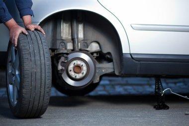 механик, изменяющий колесо современного автомобиля