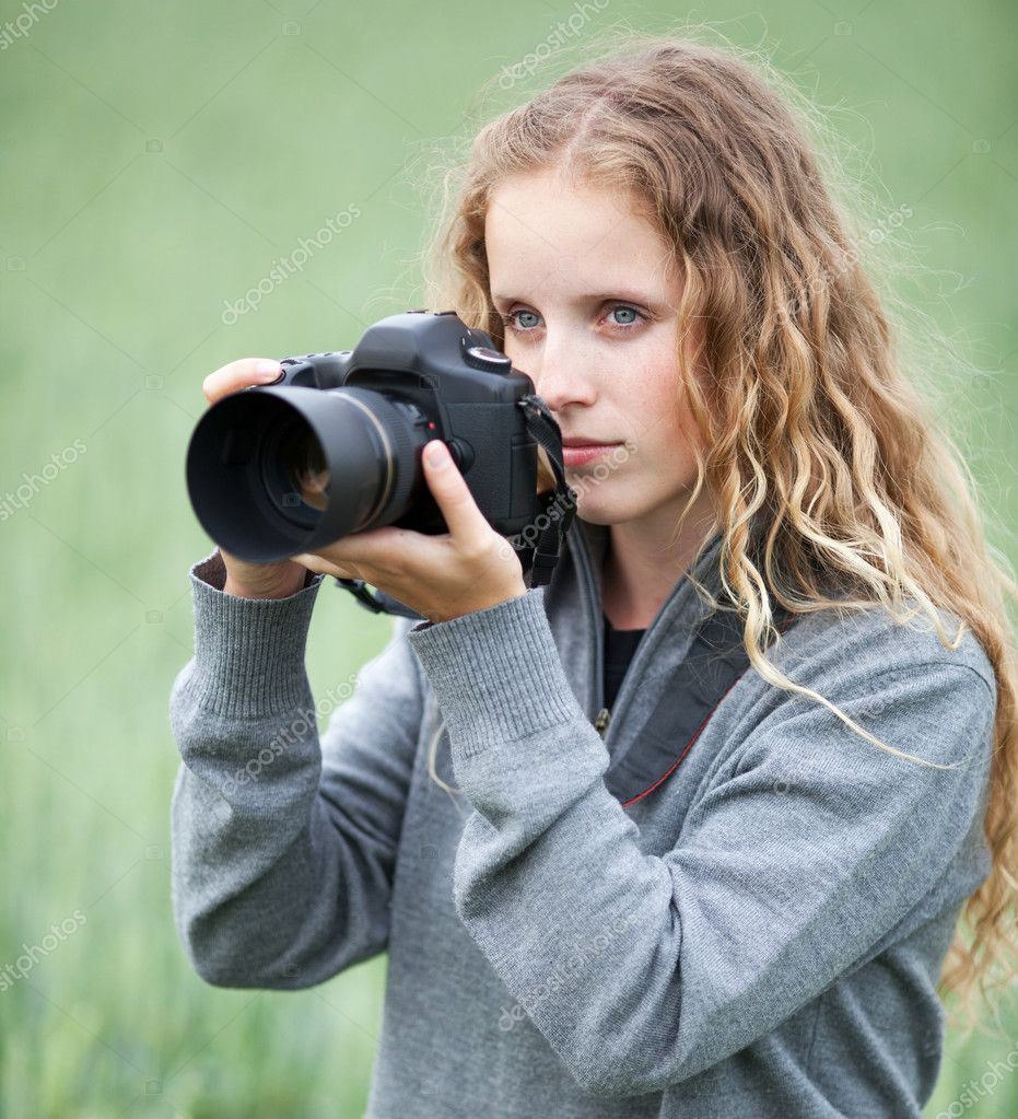 Pretty young woman with a DSLR camera outdoors taking ...
