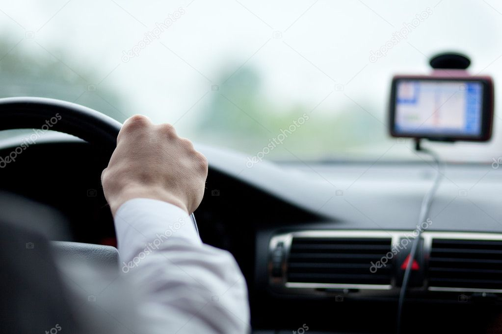 Man driving a car with his hands on the steering wheel