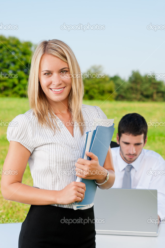 Businesswoman in sunny nature with folders smile