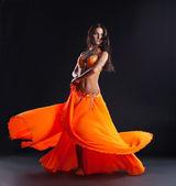 Schönheitstänzerin posiert in traditioneller orangefarbener Tracht