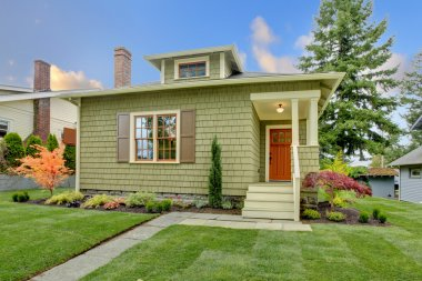 Green small craftsman style renovated house.