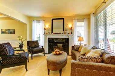 Living room in golden yellow wth fireplace and mirror