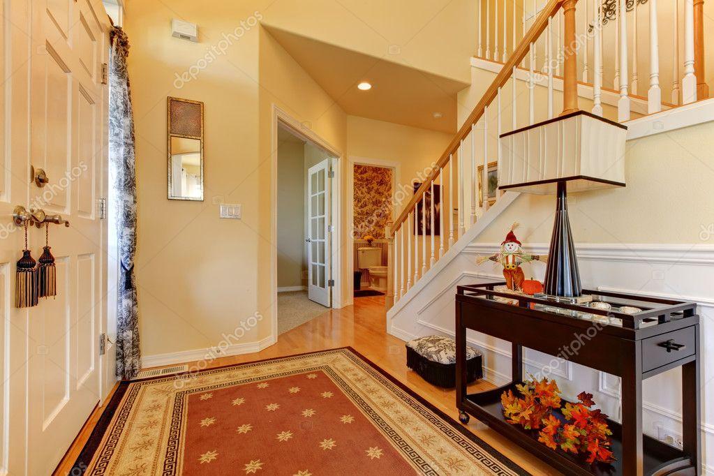 Hal en ingang met witte trap en warme gele muren u stockfoto