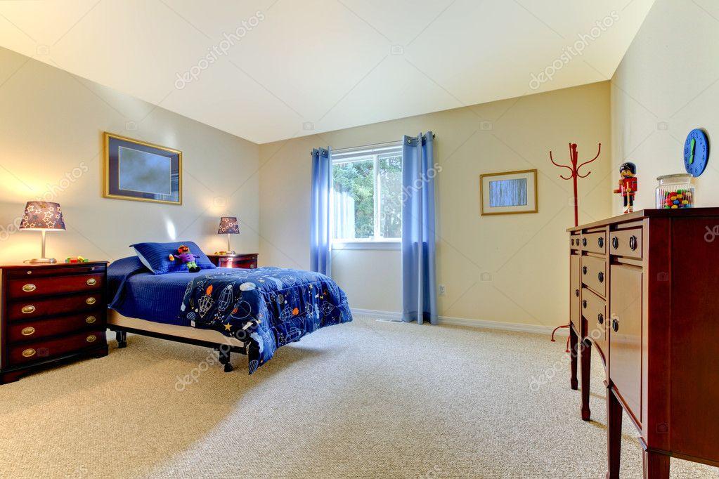 Jongens grote slaapkamer met blauwe bed en beige muren u stockfoto