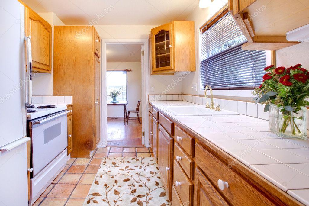 Cucina armadi in rovere con pavimento di piastrelle e fiori u foto