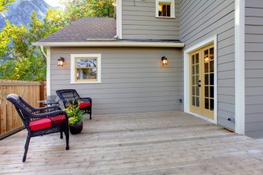 Deck with two chairs and fenced back yard near home exterior shot.