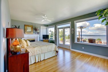 Bright large luxury blue bedroom interior with water view.