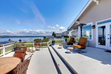 Large house deck with water view and furniture.