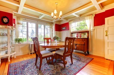Elegant red and gold dining room with antique furniture.
