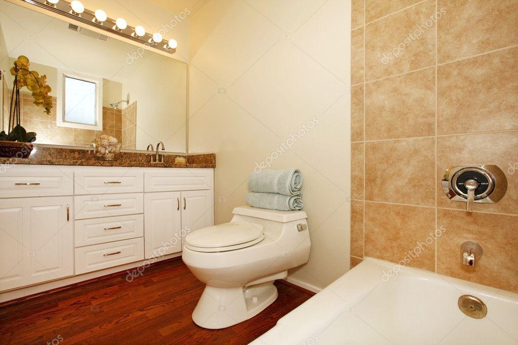 badkamer met beige keramische tegels en houten vloer — Stockfoto ...