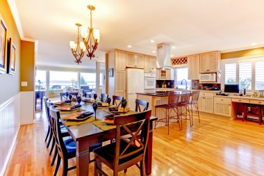 Large luxury dining room and kitchen witj shiny wood floor.
