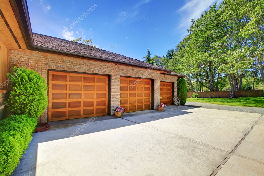 Farm house with large three car garage with nice doors.