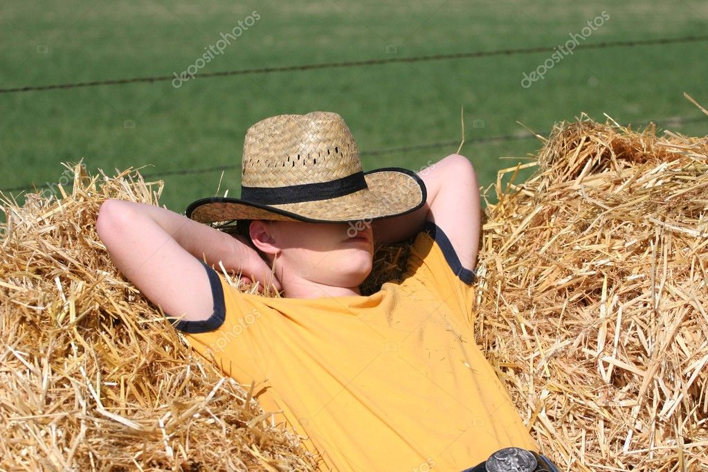 7b900e7c07943d Male cowboy sleeping in straw stack with cowboy hat pulled over face  wearing yellow shirt and blue jeans in the sun — Photo by jonalynnhansen