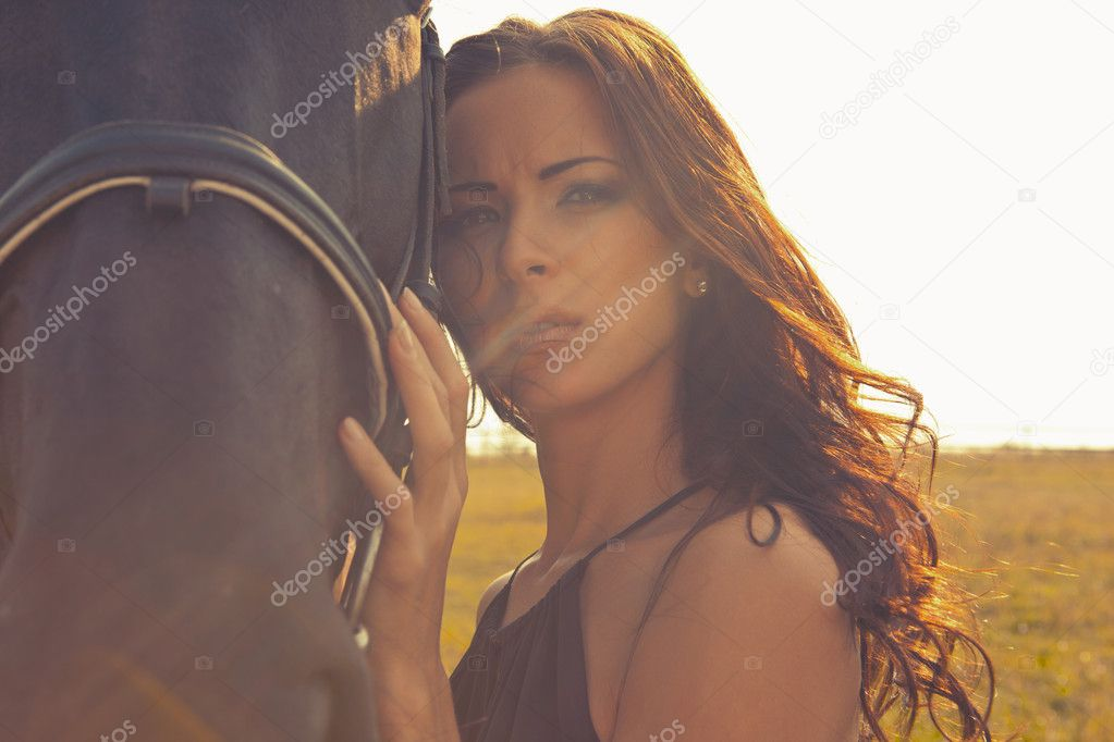Beautiful girl in a brown gown with horse on nature