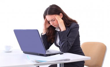 A tired woman in front of a laptop