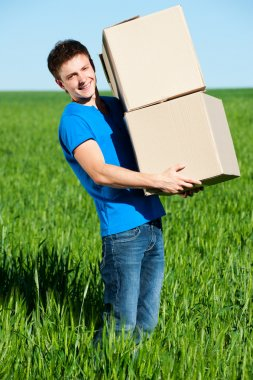 Man in blue t-shirt carrying boxes