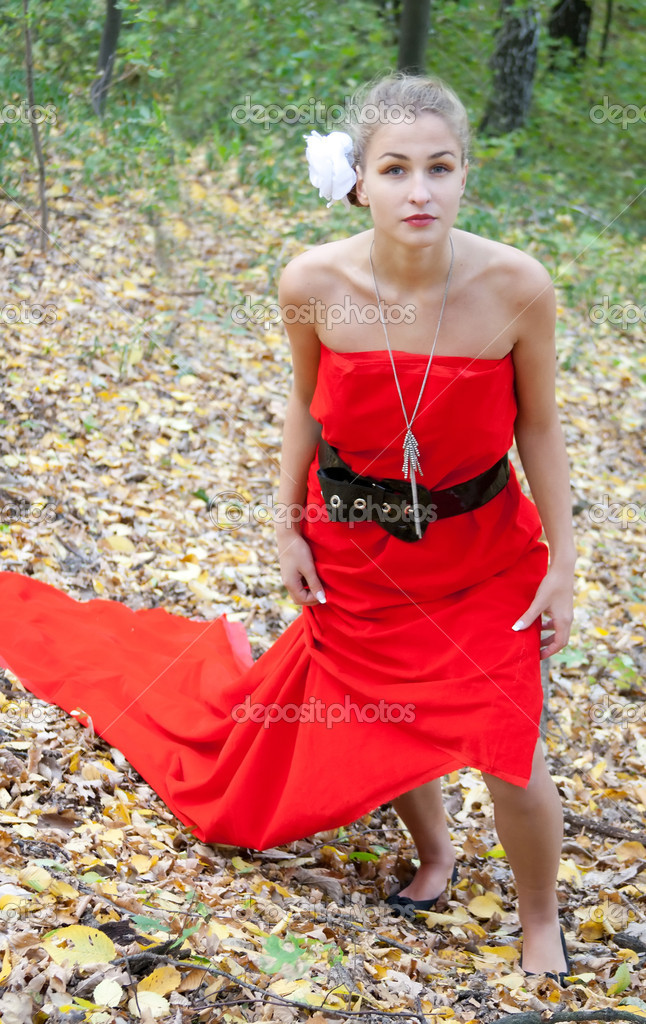 Pretty girl in red dress in the autumn in the woods