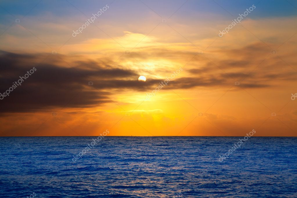 Golden sunrise with sun and clouds over sea