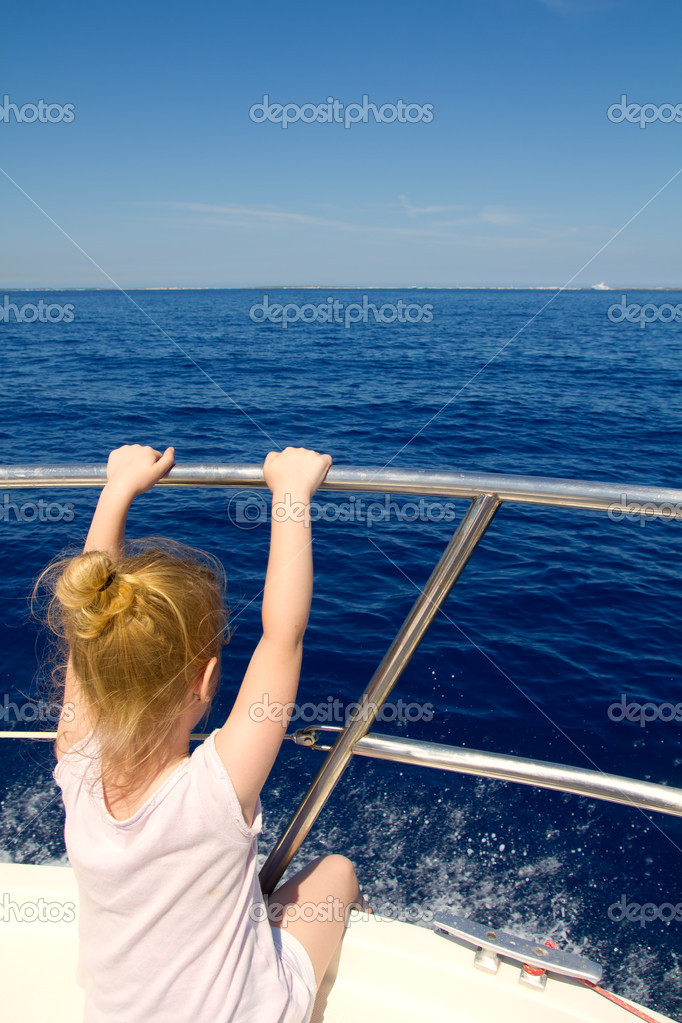 Blond little girl rear view sailing in boat