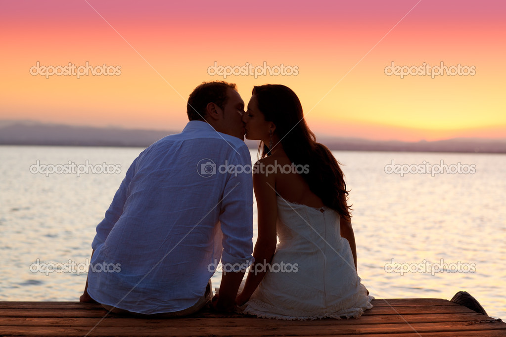 Couple kissing at sunset sitting in jetty