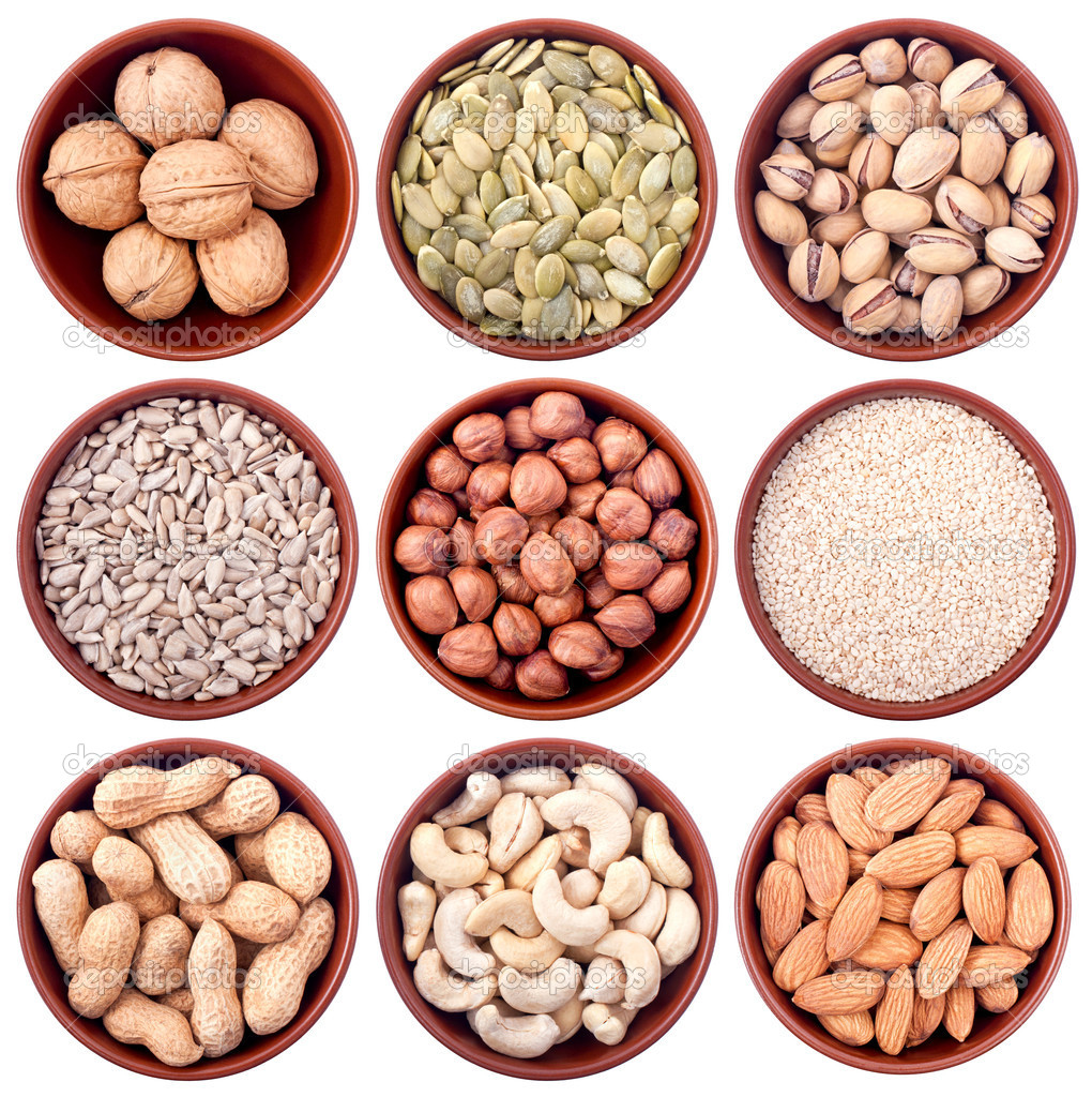 Assortment of nuts and seeds in ceramic bowls isolated on white