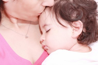 Delighted young mother taking care of her adorable baby at home