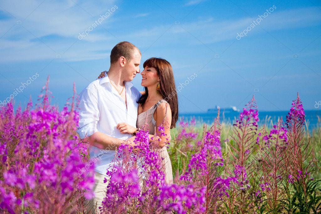 Romace among purple flowers near blue sea