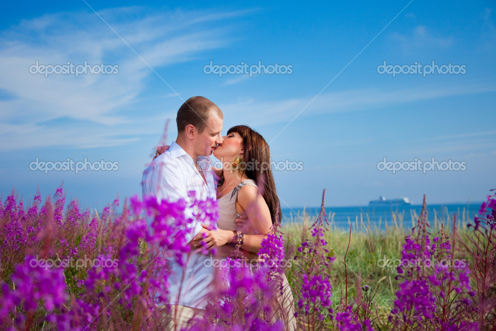 Romantic kiss among purple flowers near blue sea
