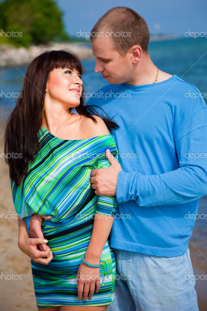 Loving couple embracing on coast of blue sea