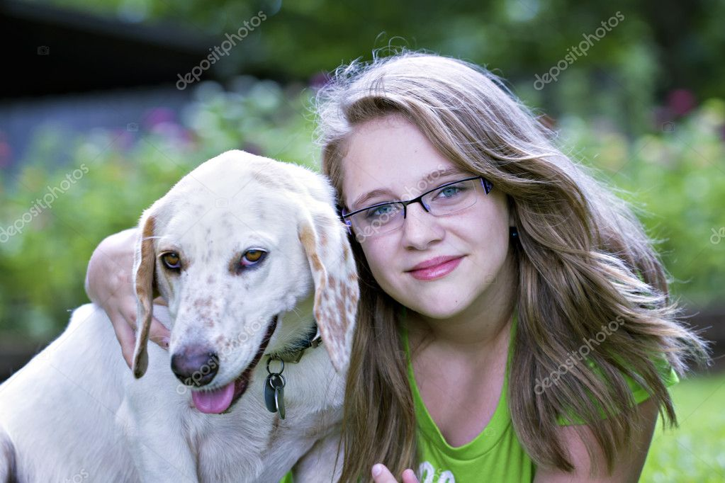 Beautiful blond teenager hugging white dog outdoors