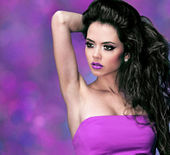 Fashion woman with long black curly hair over purple