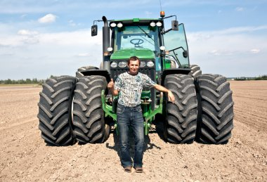 Farmer with tractor showing OK gesture
