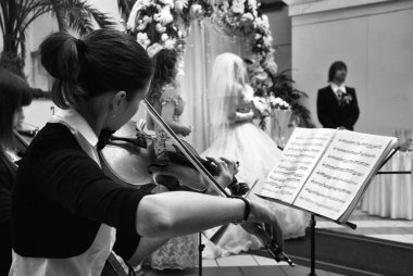 Black and white shot of girl playing the violin at the wedding ceremony