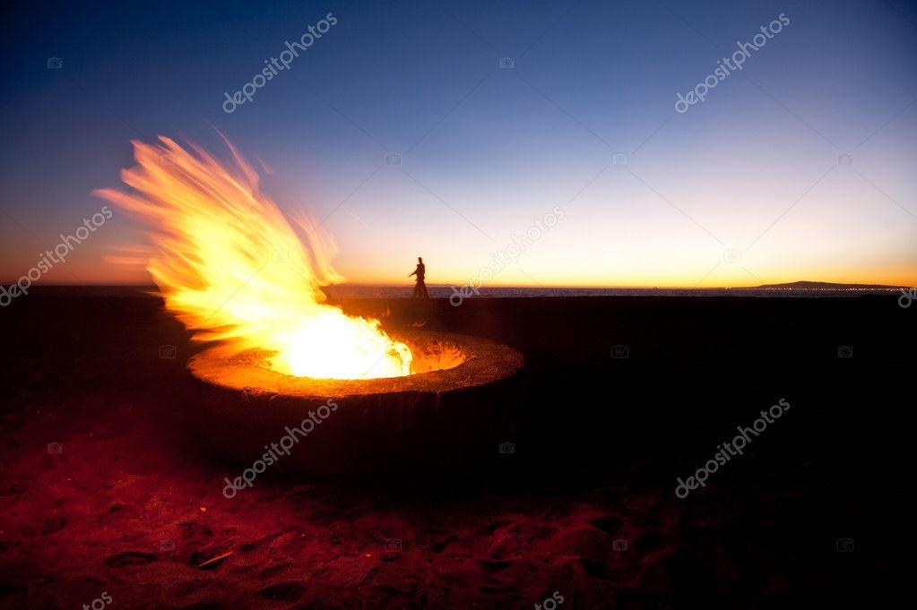 A couple walks along a beach behind a large fire during sunset. — Photo by  kelpfish - Beach Fire Pit — Stock Photo © Kelpfish #7454165