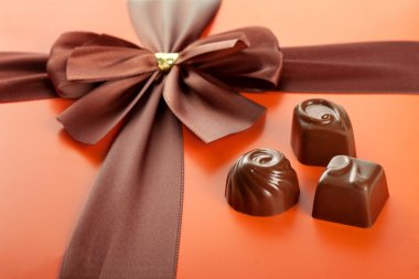 Milk chocolates and beautiful gift box with ribbon bow, closeup