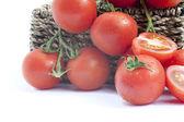 čerstvé zralé víno rajčata v rustikální koše s plátky rajčat iso