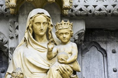 Detail close up image of Virgin Mary holding Jesus on side entrance to West