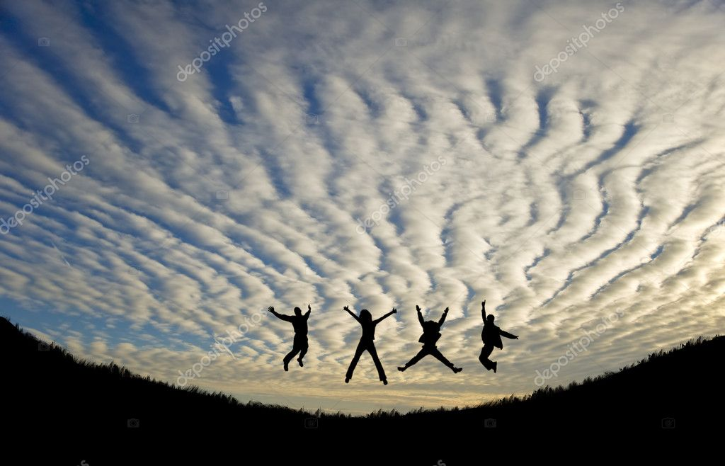Silhhuette of four adults jumping for joy or achievement against