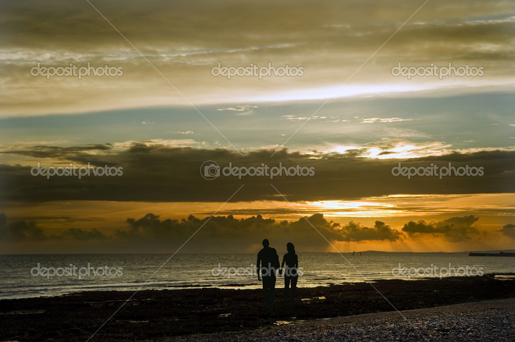 Silhouette of young couple strolling along beach at sunset