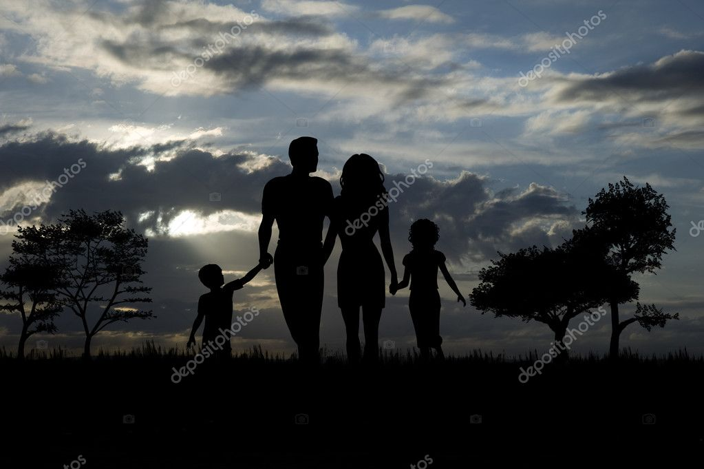 Silhouette of young family walking through fields and trees