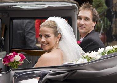 Bride and groom arrive at reception in vintage wedding car
