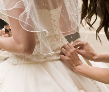 Detail of bridesmaid fixing bride's wedding dress
