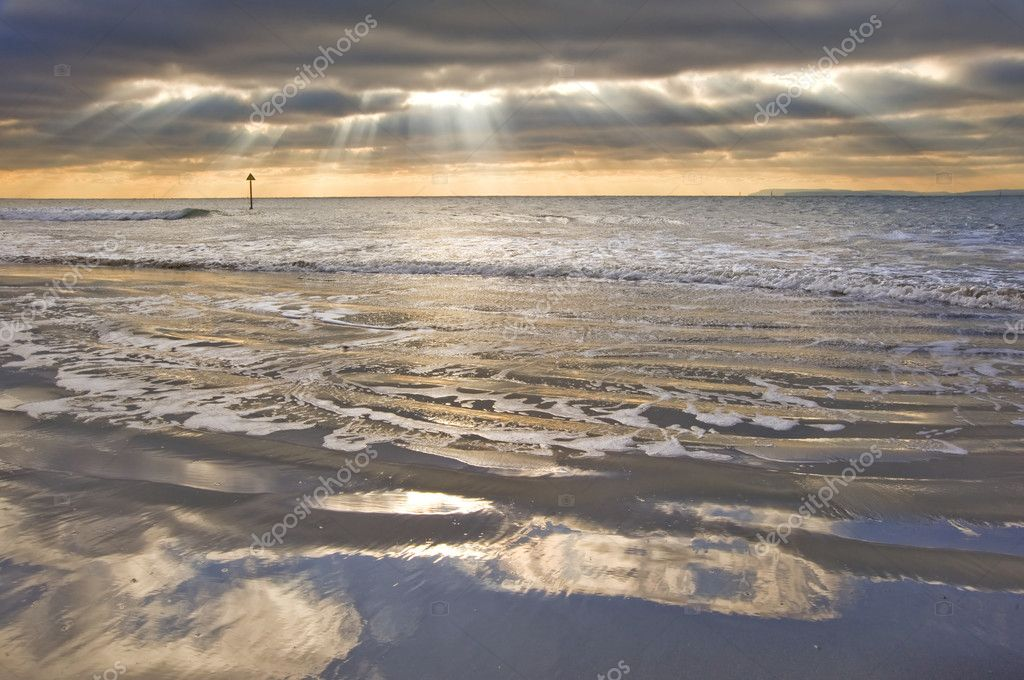 Stunning inspirational sunset image with glowing sun beams over grassy sand