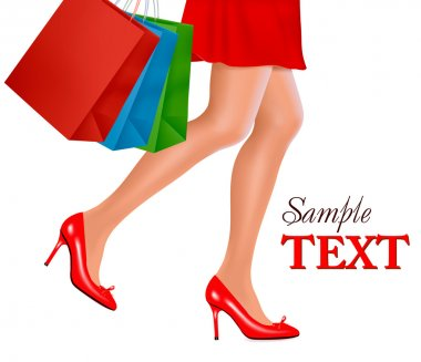 Waist-down view of shopping woman wearing red high heel shoes and carrying