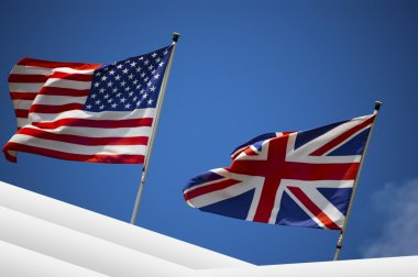 U.S. and UK flags in the blue sky