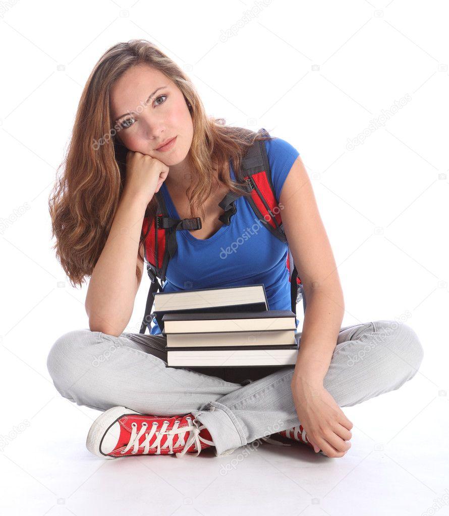 Sad teenage student girl with school study books