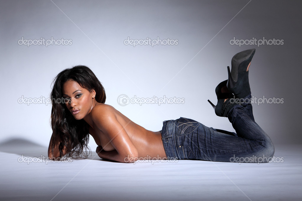 Topless african american woman lying in jeans