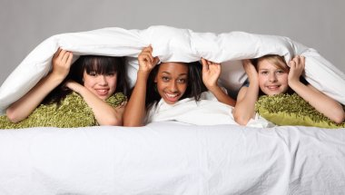 Sleepover party fun teenage girls laughing in bed