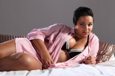 Voluptuous plus size african woman lying in bed